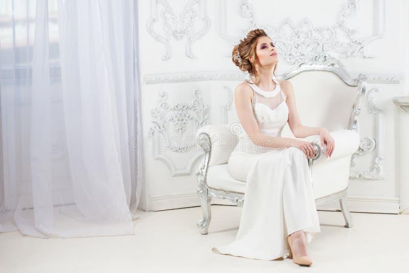 Stile di cerimonia nuziale Bella giovane sposa che si siede nella sedia di lusso nell'interno leggero lussuoso immagini stock libere da diritti