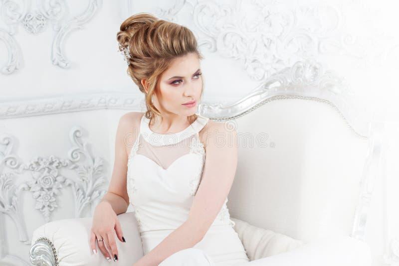 Stile di cerimonia nuziale Bella giovane sposa che si siede nella sedia di lusso nell'interno leggero lussuoso fotografia stock libera da diritti