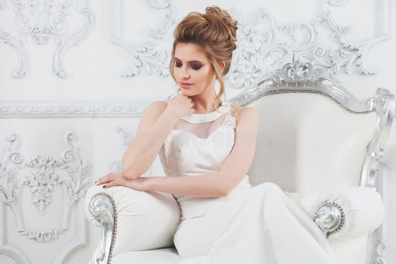 Stile di cerimonia nuziale Bella giovane sposa che si siede nella sedia di lusso nell'interno leggero lussuoso fotografia stock