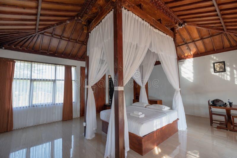 Stile di legno di balinese della camera da letto di architettura con la tenda della villa tropicale fotografie stock libere da diritti
