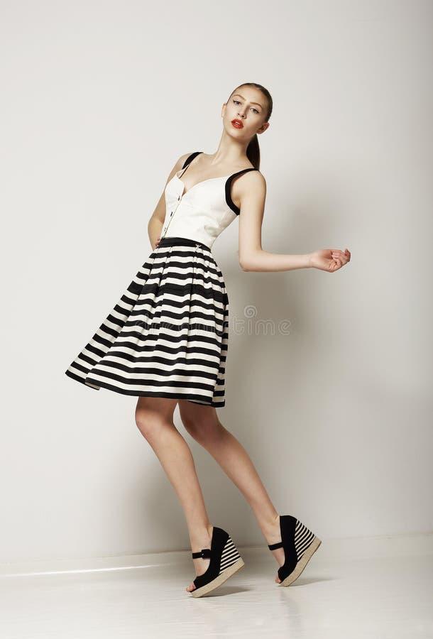 Stile di modo. Giovane cliente felice al contrario Grey Skirt a strisce. Movimento immagine stock