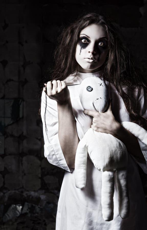 Stile di orrore sparato: ragazza pazza sconosciuta con la bambola del moppet ed ago in mani immagini stock