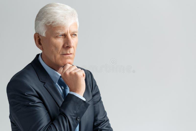 Stile di vita di affari Condizione dell'uomo d'affari isolata sul mento commovente grigio premuroso fotografia stock