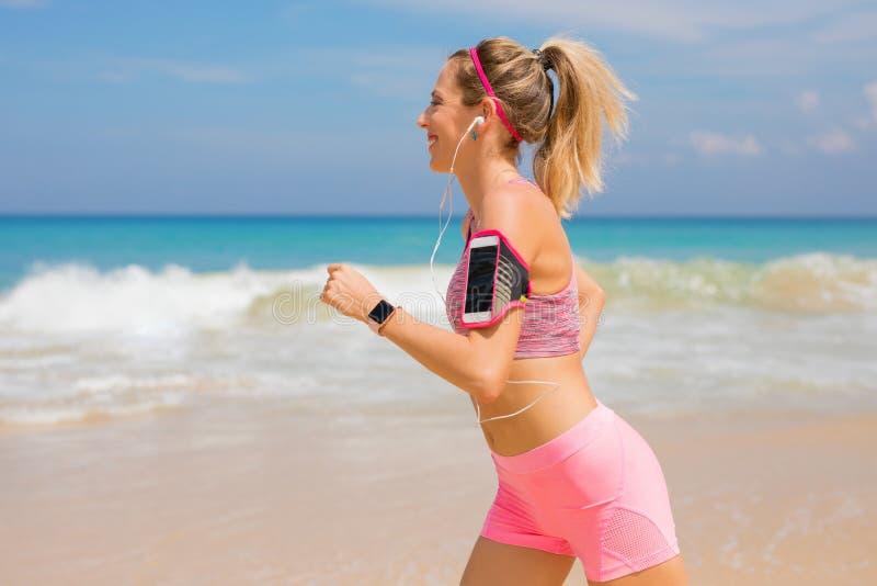 Stile di vita attivo vivente della donna, corrente sulla spiaggia fotografia stock
