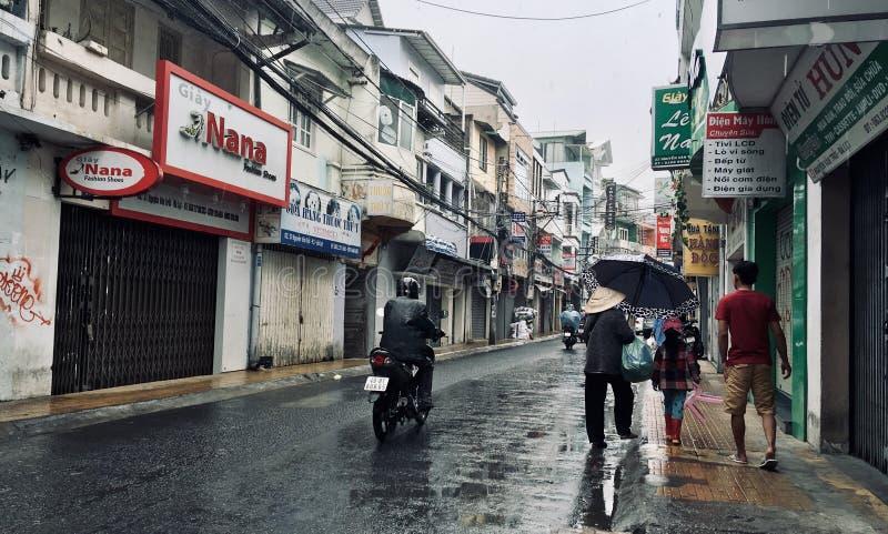 Stile di vita del Vietnam, la gente che cammina sulla strada nella pioggia immagine stock