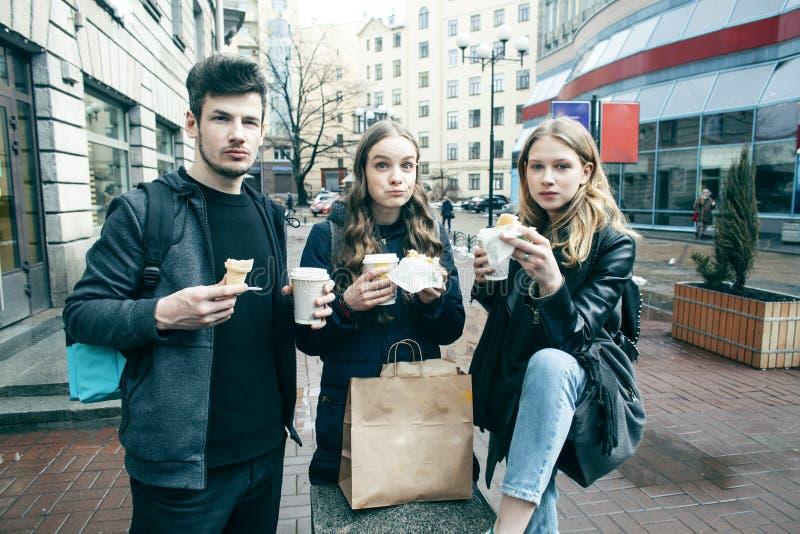 Stile di vita e concetto della gente: due ragazze e tipo che mangiano alimenti a rapida preparazione sulla via che si diverte ins fotografia stock libera da diritti