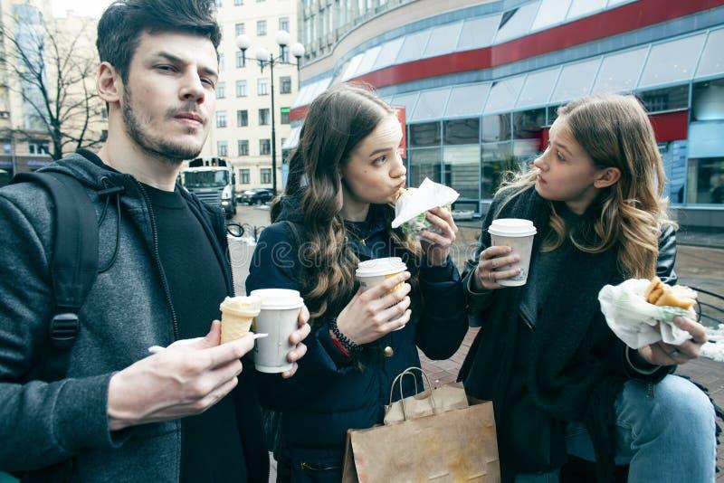 Stile di vita e concetto della gente: due ragazze e tipo che mangiano alimenti a rapida preparazione sulla via che si diverte ins fotografie stock libere da diritti
