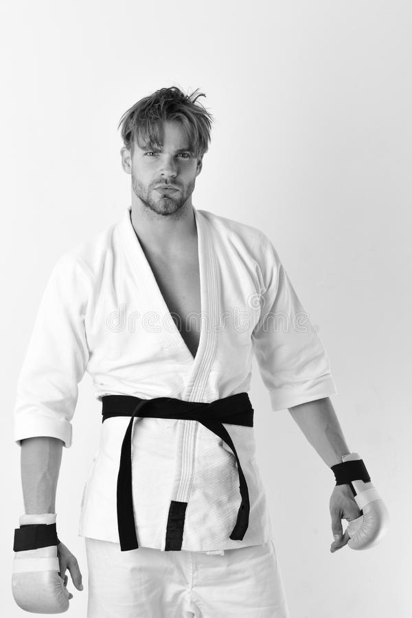 Stile di vita e concetto sani di pugilato Il tipo posa in kimono bianco che porta i guantoni da pugile dorati fotografia stock