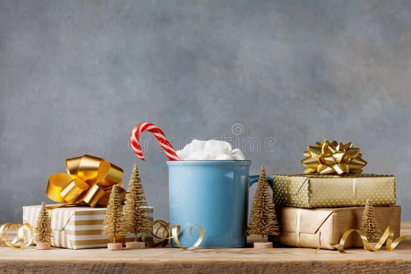 Stile di vita di inverno con la tazza di cacao caldo con le caramelle gommosa e molle e regalo di Natale o scatole e decorazioni  fotografia stock libera da diritti