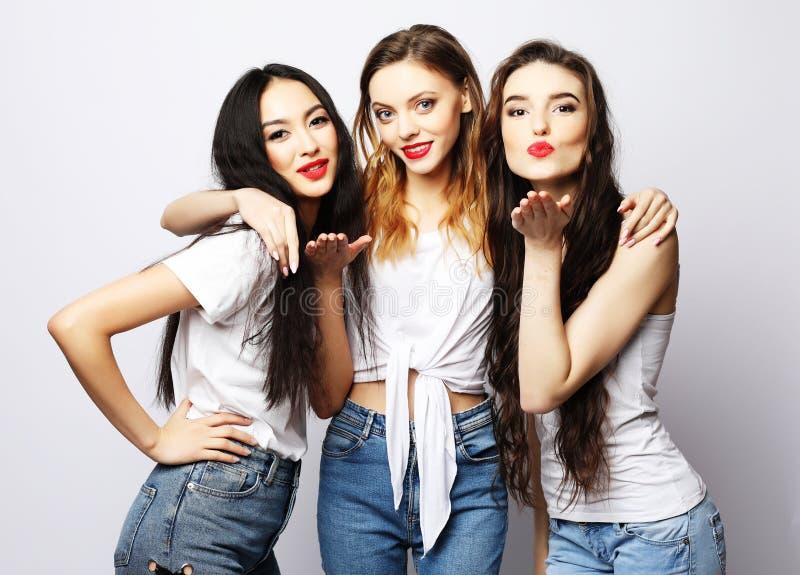 Stile di vita, modo e concetto della gente - un gruppo di uso di tre amici di ragazze casuale fotografia stock