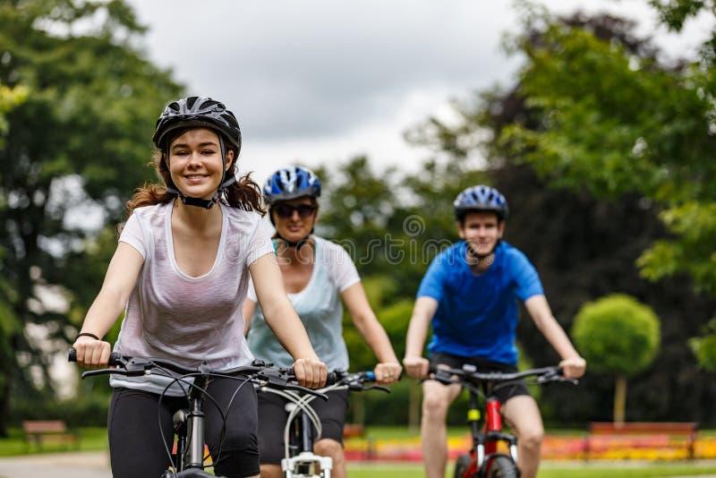 Stile di vita sano - biciclette di guida della gente nel parco della citt? fotografie stock