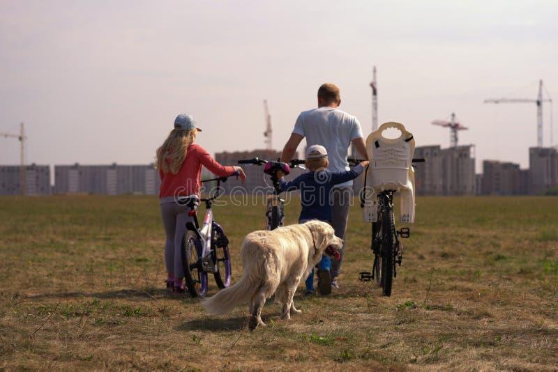 Stile di vita sano - famiglia con le biciclette e un cane che cammina lungo il campo vicino alla città fotografie stock