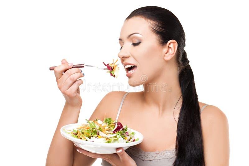 Stile di vita sano - giovane donna che mangia insalata fotografia stock