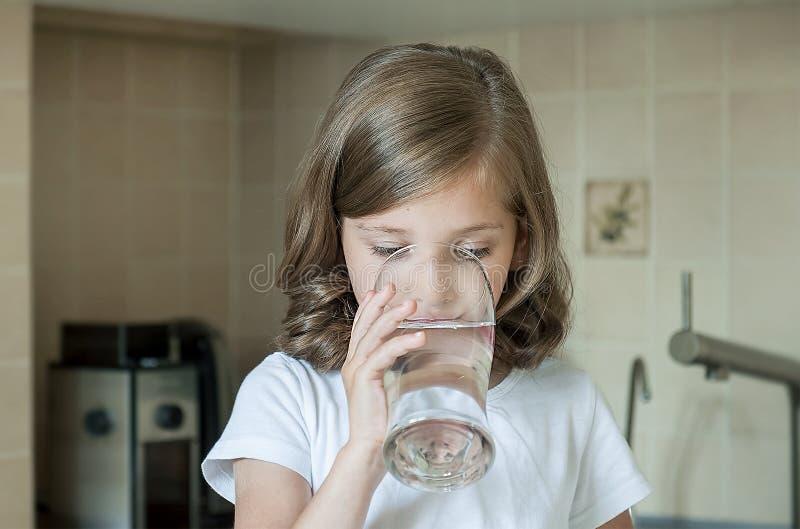 Stile di vita sano Ritratto della ragazza felice con vetro Bambino bello che beve acqua dolce nella cucina a casa fotografie stock libere da diritti