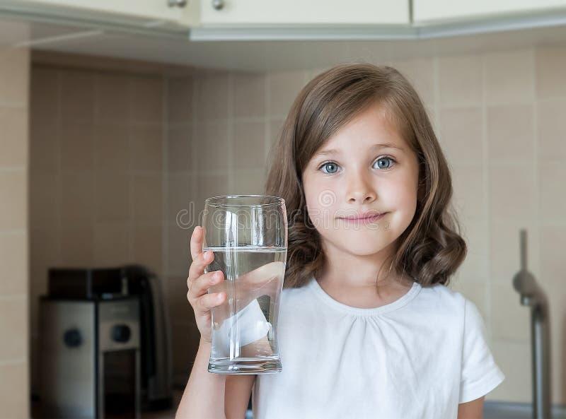 Stile di vita sano Ritratto della ragazza sorridente felice con vetro Bambino che beve acqua dolce nella cucina a casa immagini stock libere da diritti