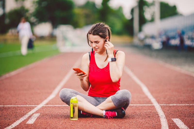 Stile di vita sano di tema, musica di sport la giovane donna caucasica riposa la pedana mobile di seduta che esegue lo stadio di  immagine stock
