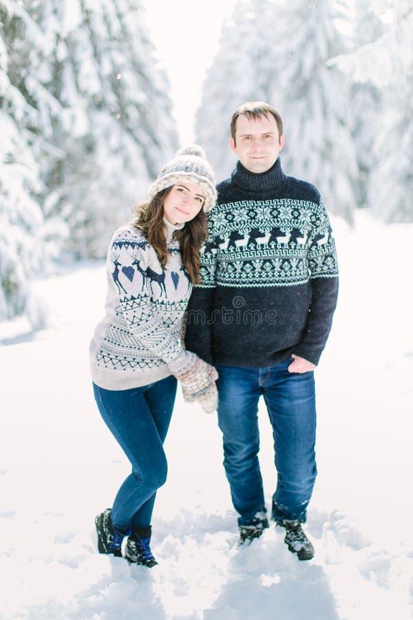 Stile di vita sparato di giovani coppie felici in vestiti tricottati di inverno che camminano nella foresta nevosa, spendendo vac fotografia stock