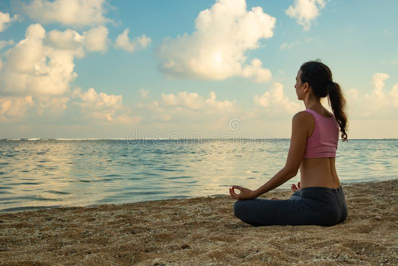 Stile di vita di yoga Yoga meditante e di pratica della giovane donna e pranayama con il mudra gyan alla spiaggia, Bali immagini stock libere da diritti
