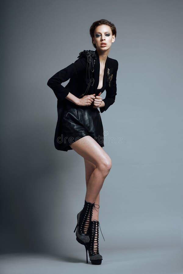 Stile di Vogue. Modello di moda alla moda della donna in vestiti ed in stivali neri d'avanguardia. Personalità immagini stock libere da diritti
