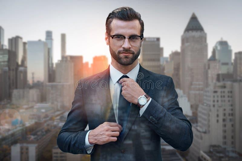 Stile perfetto Esperto sicuro in affari in vetri che regolano cravatta mentre stando contro del paesaggio urbano di mattina fotografie stock libere da diritti