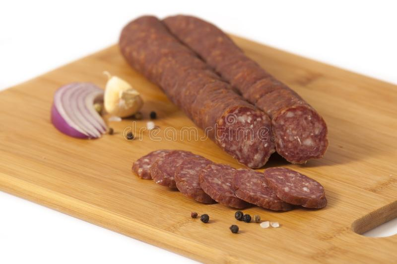 Stile serbo del salame duro - kobasica di Cajna, su un bordo bianco isolato su fondo bianco - kobasica di Cajna fotografie stock