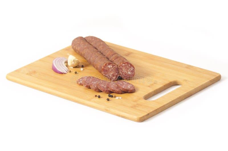 Stile serbo del salame duro - kobasica di Cajna, su un bordo bianco isolato su fondo bianco - kobasica di Cajna fotografia stock libera da diritti