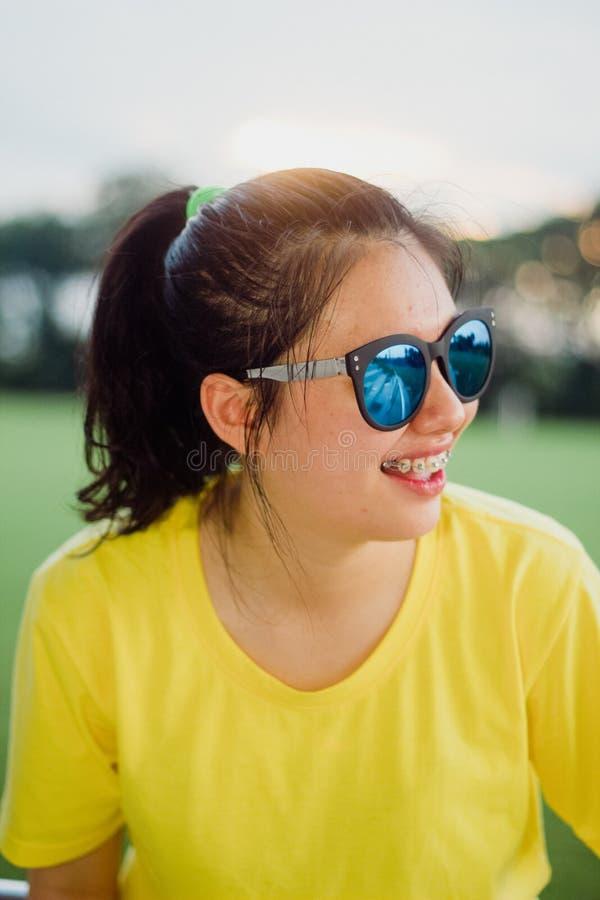 Stile teenager adorabile della via della ragazza che sorride con gli occhiali da sole nell'ambito del sole fotografie stock