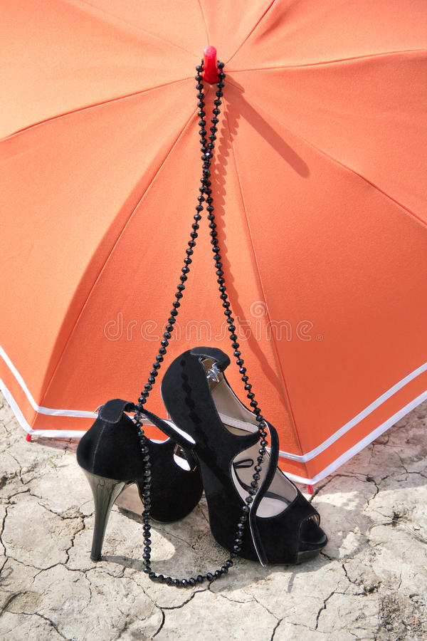 Stiletto heels, necklace and umbrella on a cracked earth royalty free stock images