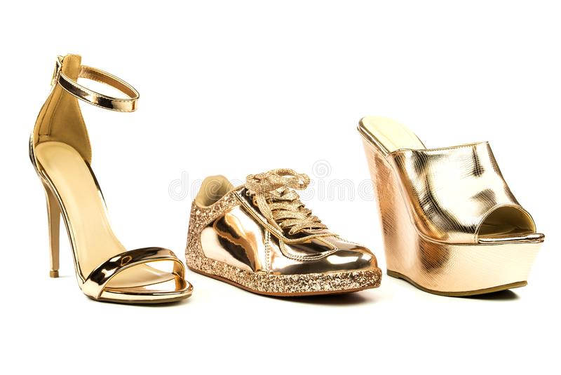 Stiletto high heels, mules and sneakers in metallic colors. Stiletto high heels with ankle strap, platform mules and fashionable sneakers in shiny metallic stock photos