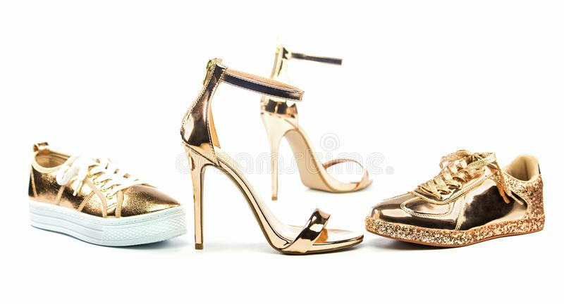 Stiletto high heels and sneakers in metallic colors. Stiletto high heels with ankle strap and fashionable sneakers in shiny metallic color, on white backgroud royalty free stock photos