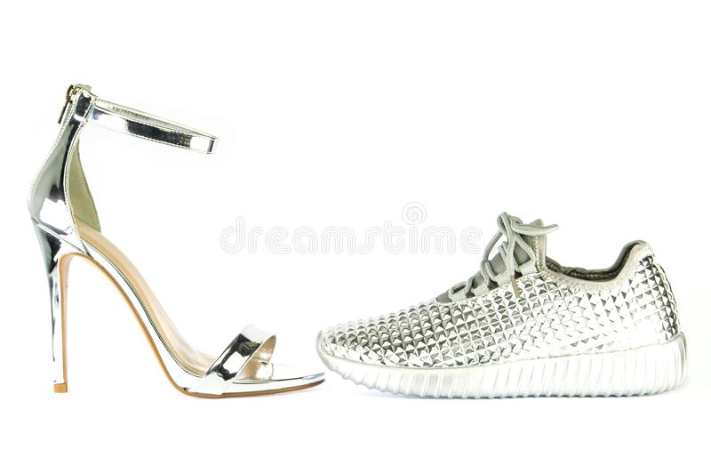 Stiletto high heels and sneakers in metallic silver. Stiletto high heels with ankle strap and fashionable sneakers in shiny silver metallic color, isolated on royalty free stock images