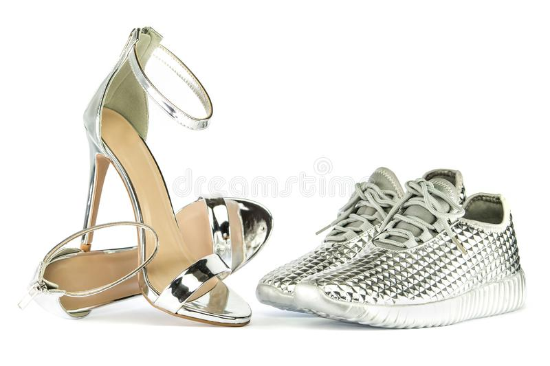 Stiletto high heels and sneakers in metallic silver. Stiletto high heels with ankle strap and fashionable sneakers in shiny silver metallic color, isolated on royalty free stock photos