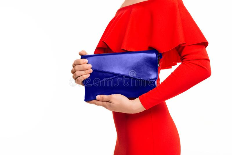 Stilfull affärskvinna i en röd klänning som rymmer en blå modekoppling royaltyfri fotografi