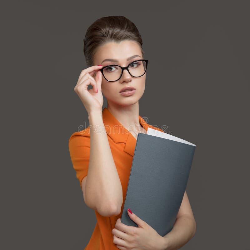 Stilfull affärskvinna med en mapp i hennes händer Den unga specialisten rätar ut exponeringsglas arkivbilder