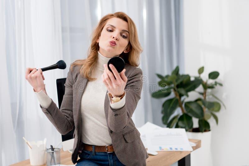 stilfull affärskvinna som ser spegeln, medan applicera makeup på arbetsplatsen arkivfoton