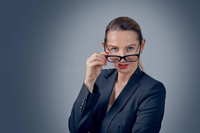 Stilfull affärsledare som plirar över hennes exponeringsglas royaltyfri foto