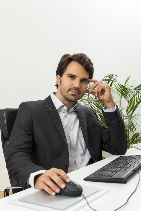 Stilfull affärsman i ett dräktsammanträde på hans skrivbord royaltyfri foto