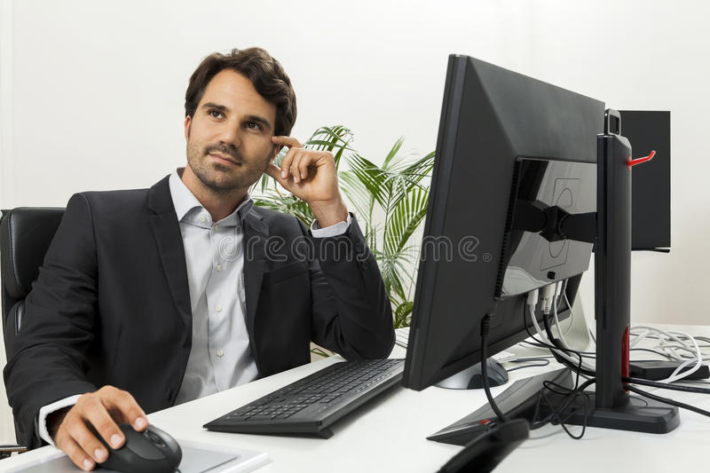 Stilfull affärsman i ett dräktsammanträde på hans skrivbord arkivfoto