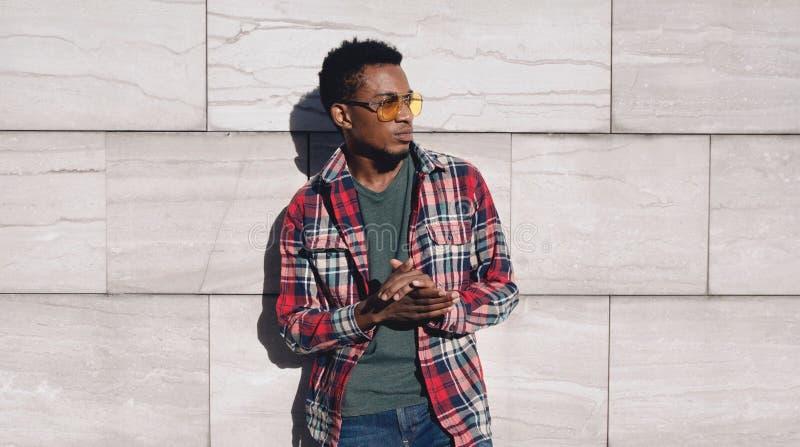Stilfull afrikansk man för stående som bär den röda plädskjortan som bort ser, grabb som poserar på stadsgatan, grå tegelstenvägg royaltyfria foton