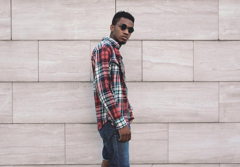 Stilfull afrikansk man för stående som bär den röda plädskjortan, grabb som poserar på stadsgatan över den gråa tegelstenväggen royaltyfri foto