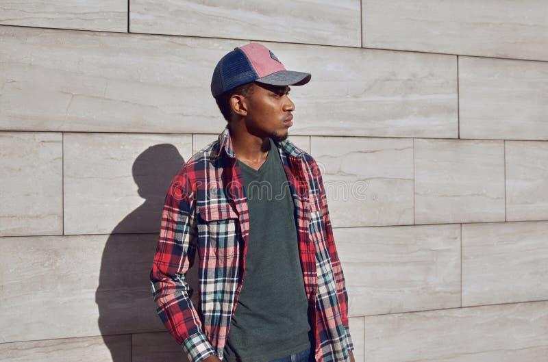 Stilfull afrikansk man som bär den röda plädskjortan, baseballmössa som bort ser, ung grabb som poserar på stadsgatan, grå tegels fotografering för bildbyråer