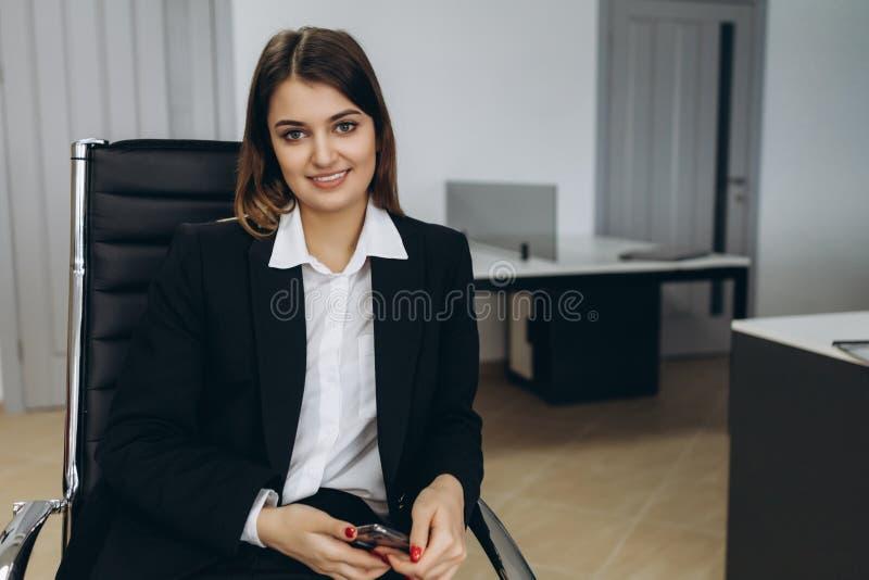 Stilfull attraktiv ung affärskvinna med ett älskvärt leende som framme sitter av en tabell i kontoret som grinar på kameran arkivfoto