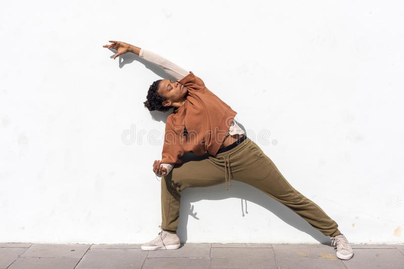 Stilfull attraktiv ung kvinnlig löpare i den svarta sportswearen som utomhus gör uppvärmningsrutin, innan att köra mot väggen royaltyfri bild