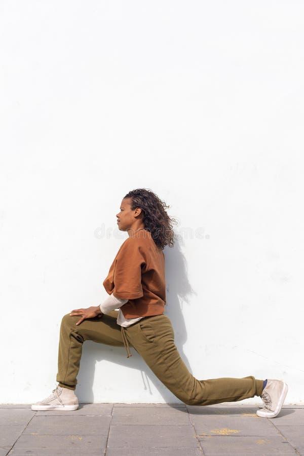 Stilfull attraktiv ung kvinnlig l?pare i den svarta sportswearen som utomhus g?r uppv?rmningsrutin, innan att k?ra mot v?ggen royaltyfria bilder