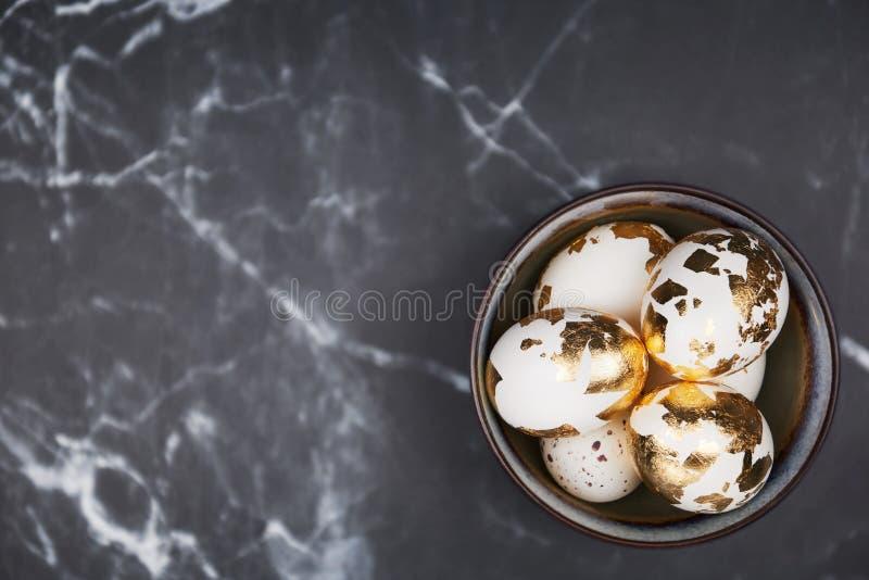 Stilfull bakgrund, vita ägg dekorerade med guld- folie i rus royaltyfria bilder