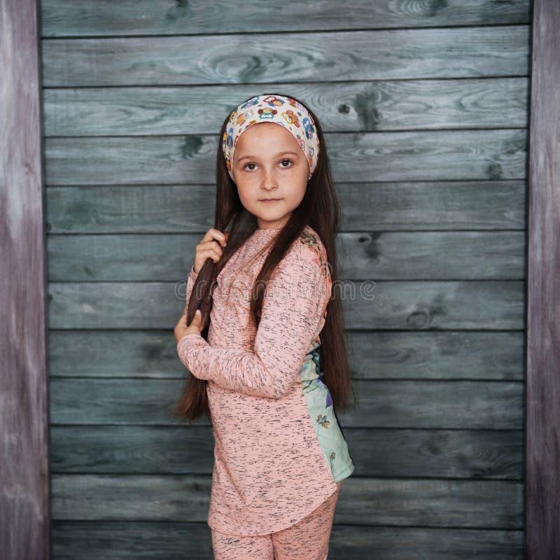 Stilfull benägenhet för tonårs- flicka mot en vägg arkivfoton