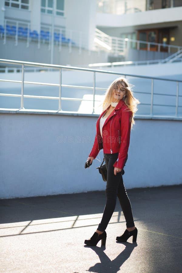 Stilfull blond flicka som bär det röda omslaget som går ner gatan med solljus arkivbilder