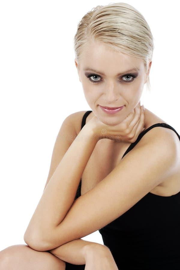 Stilfull blond kvinna i en enkel elegant tillbaka klänning arkivfoto