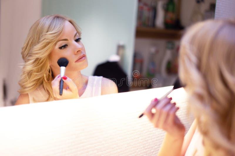 Stilfull blond kvinna som applicerar makeup vid rougeborsten i spegel royaltyfri bild