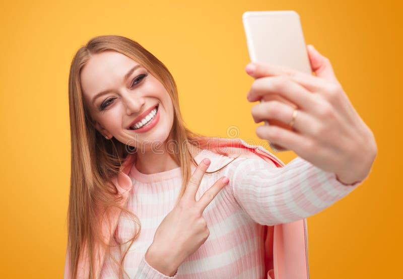 Stilfull blond kvinna som tar selfie på apelsinen royaltyfri bild